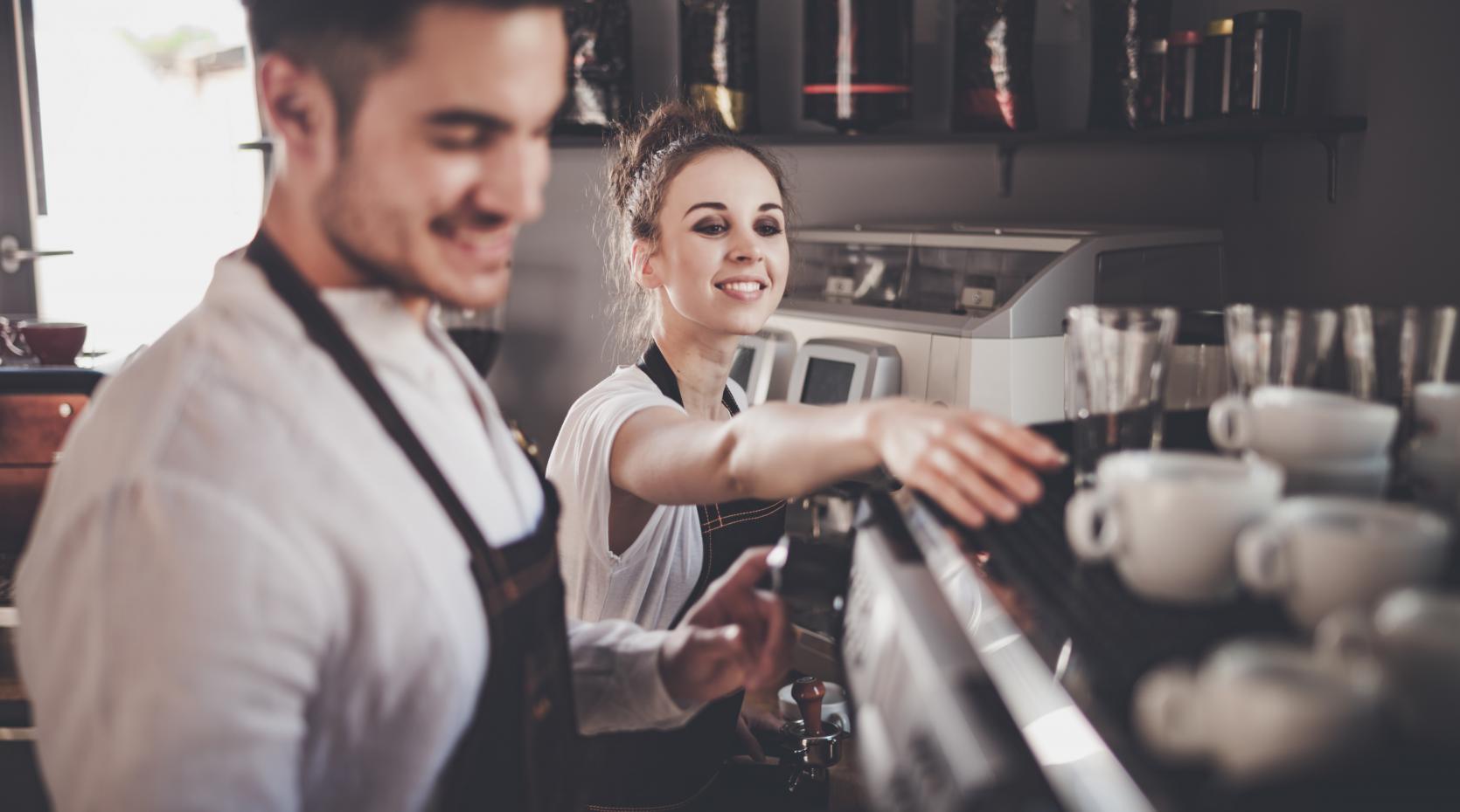 Man och kvinna arbetar vid en kaffemaskin