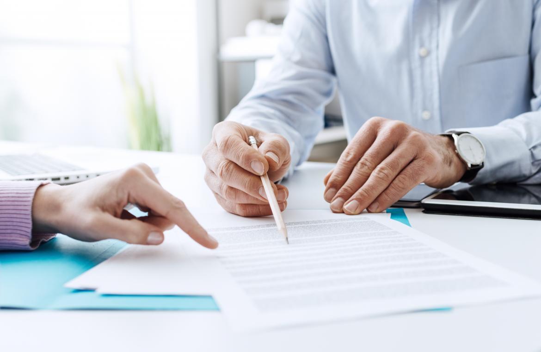 Man pekar med sin penna på ett dokument
