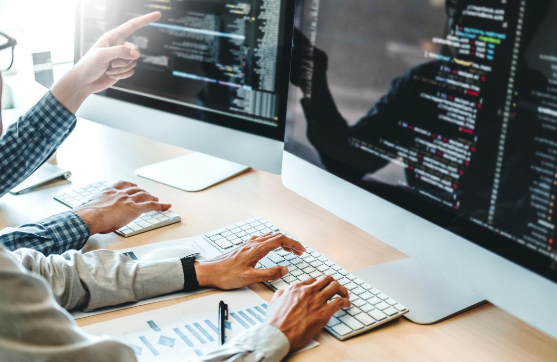 Händer på ett tangentbord framför en dataskärm